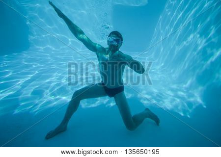 Man posing underwater in swimming pool at resort