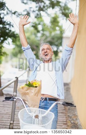 Excited man with arms raised and bicycle standing outdoors