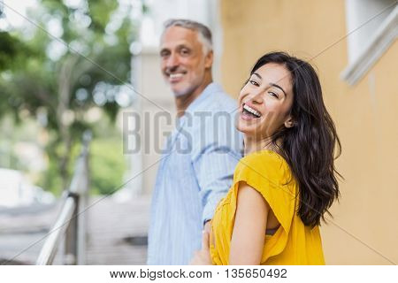 Portrait of happy woman with man standing in city