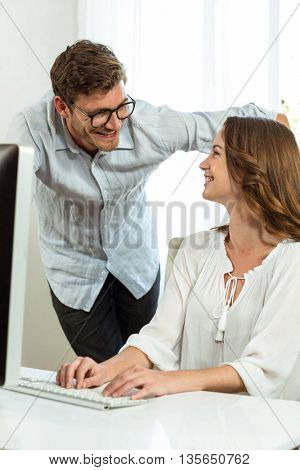 Male and female collegues smiling while using computer at desk in office