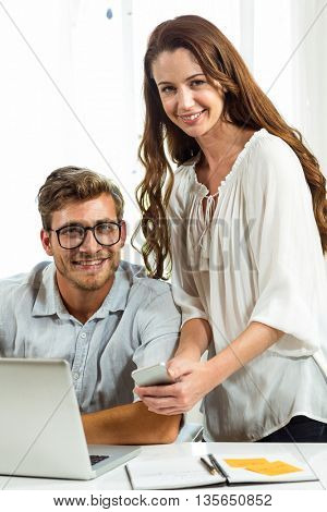 Portrait of man and woman using mobile phone at desk in office