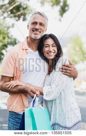 Portrait of happy couple with shopping bags embracing outdoors
