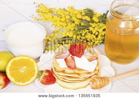 Pancakes with fruits honey and a cup of milk