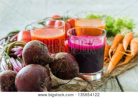 Selection of vegetable juices in glasses and ingredients, copy space