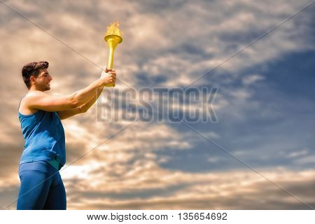 Low angle view of sportsman holding a cup against cloudy sky