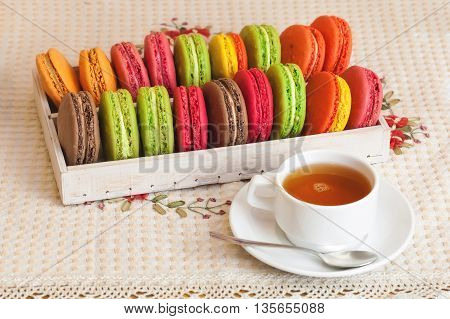 Traditional French Colorful Macarons In A Box, Cup Of Tea