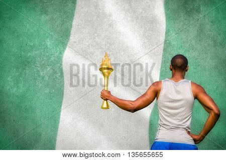 Rear view of sportsman holding a cup against digitally generated nigerian national flag