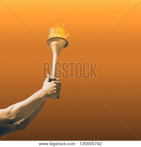 Low angle view of sportsman holding a cup against orange sky