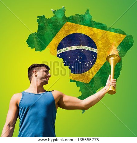 Low angle view of sportsman holding a cup against green brazil outline with flag