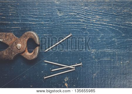 nails and old rusty tongs on blue wooden background