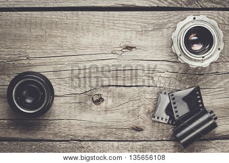 retro camera lenses and negative film on wooden table