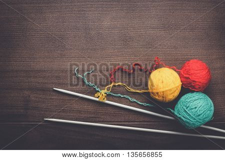 knitting needles and colorful ball of threads on wooden background