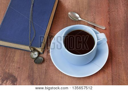 A cup of black coffee in a teal blue cup with a book and a vintage chain watch on a dark wooden background with copyspace; 'Time to Read (or Study)' concept