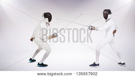 Man wearing fencing suit practicing with sword against grey background
