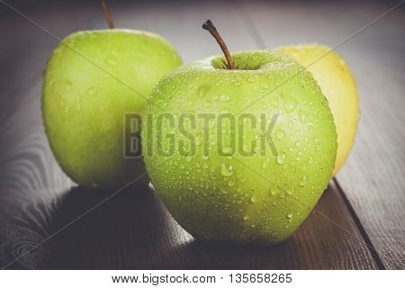 fresh green apples on the brown wooden table