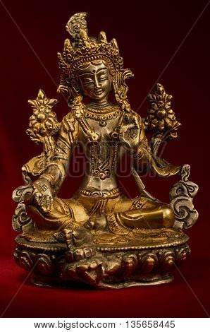 Statuette of Green Tara on a red background. Vajrayana deity quick to help and protection. Om tare tuttare ture soha.