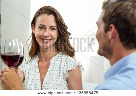 Smiling woman with husband toasting wineglasses at home