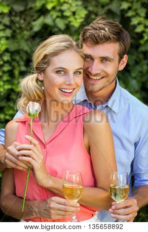 Portrait of happy man giving flower to woman while holding wineglasses at front yard