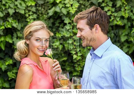 Happy man giving flower to woman while holding wineglasses at front yard