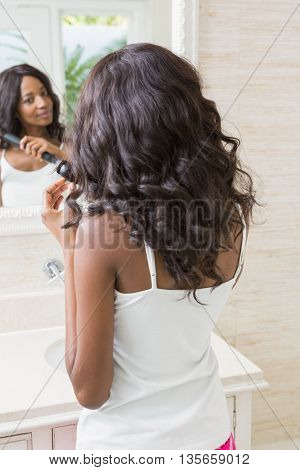 Young woman straightening hair in the bathroom