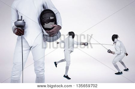 Swordsman holding fencing mask and sword against grey vignette