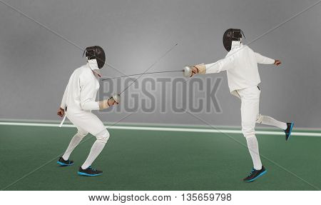 Man wearing fencing suit practicing with sword against digitally generated image of bicolored background