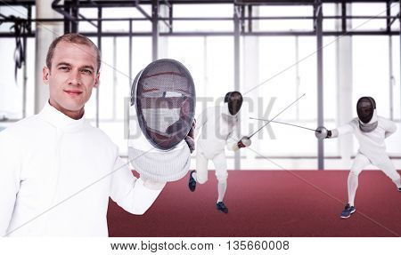 Swordsman holding fencing mask against view of a gym