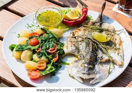 Fresh fish sea bream, bream with salt herbs and pepper prepares grilled.