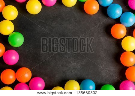 Chalkboard with copy space and colorfull plastic balls (play and learn concept)