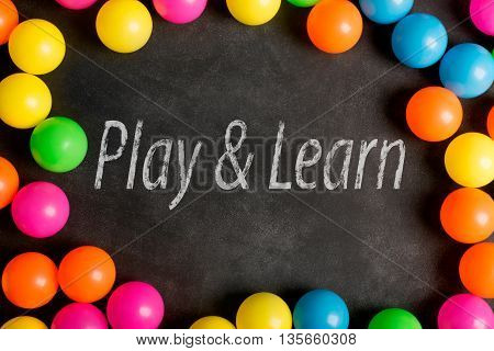 Chalkboard with inscription and colorfull plastic balls (play and learn concept)