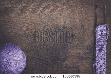 knitting needles and ball of threads on wooden background