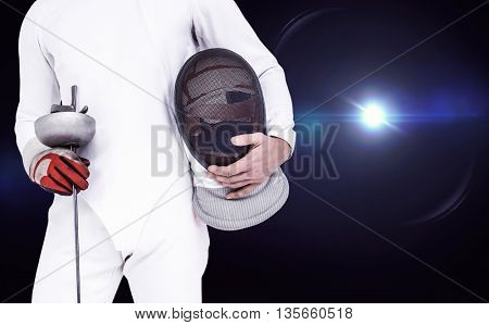 Swordsman holding fencing mask and sword against view of lights