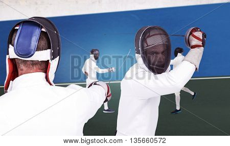 Man wearing fencing suit practicing with sword against digitally generated image of bi colored background