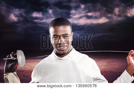 Portrait of swordsman standing with sword against dark cloudy sky