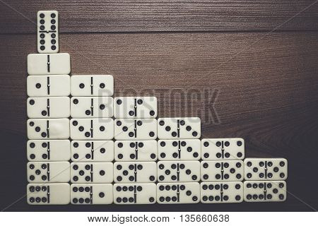 leadership concept. domino pieces forming stairs over wooden background