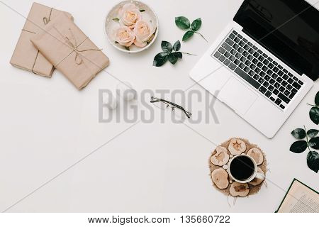 Workspace with diary, pen, vintage white tray, pink rose, croissants and coffee on white background. Top view, flat lay
