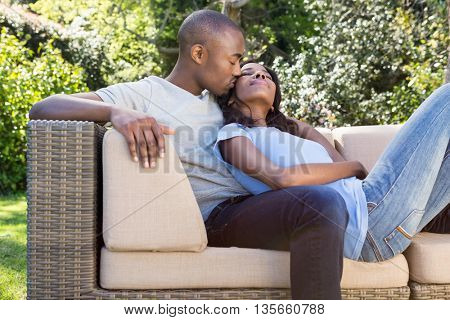 Young man kissing woman on her cheeks in the park