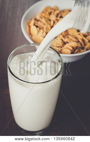 milk pouring into glass and bowl with cornflakes on the table