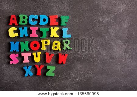 ABC alphabet (letters) on the black chalkboard with copy space