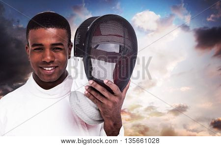 Swordsman holding fencing mask against country scene