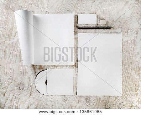 Branding identity set on light wooden background. Blank template for branding identity. Blank stationery set. Template for design portfolios. Top view.