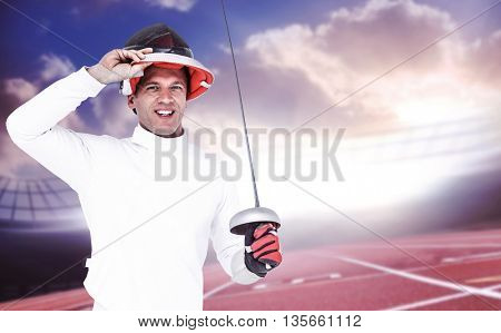 Man wearing fencing suit practicing with sword against race track