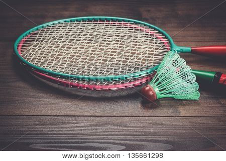 shuttlecock and badminton racket on brown wooden background