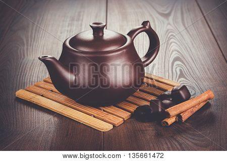 teapot with hot tea and cinnamon sticks on the table