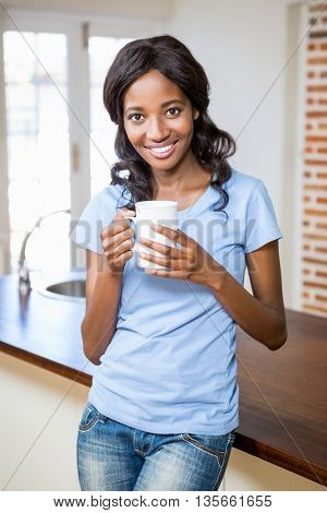 Portrait of young woman holding coffee mug in the kitchen