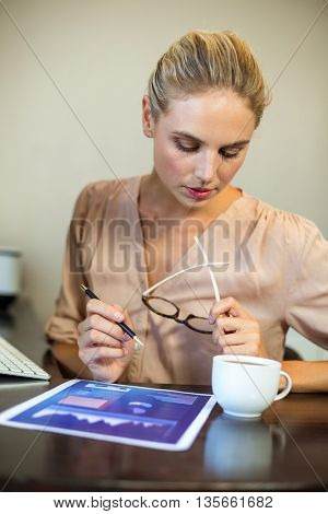 Young businesswoman looking at document with coffee cup on desk at office