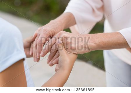 Closeup of grandmother and granddaughter holding hands. Old woman and little girl holding hands together. Closeup of hands of senior old woman and young girl outdoor.