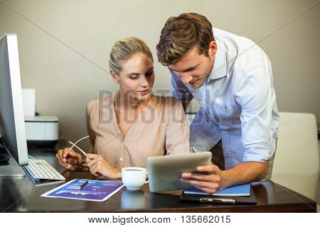 Young colleagues using digital tablet at desk in office