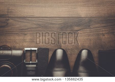 brown shoes, socks, belt, and film camera on wooden table