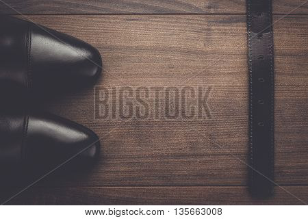 brown shoes and belt on the wooden table